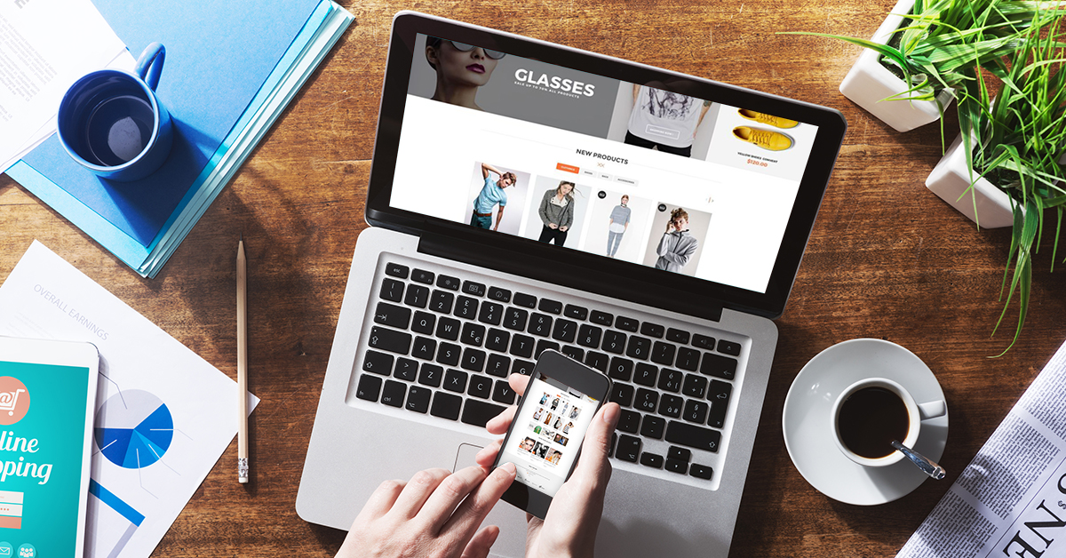 Online shopping website on laptop screen with female hands using a smartphone